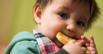 Bebê morde bolacha; introdução de alimento deve ser feita de forma gradativa  (Foto: Bia Fotografia)