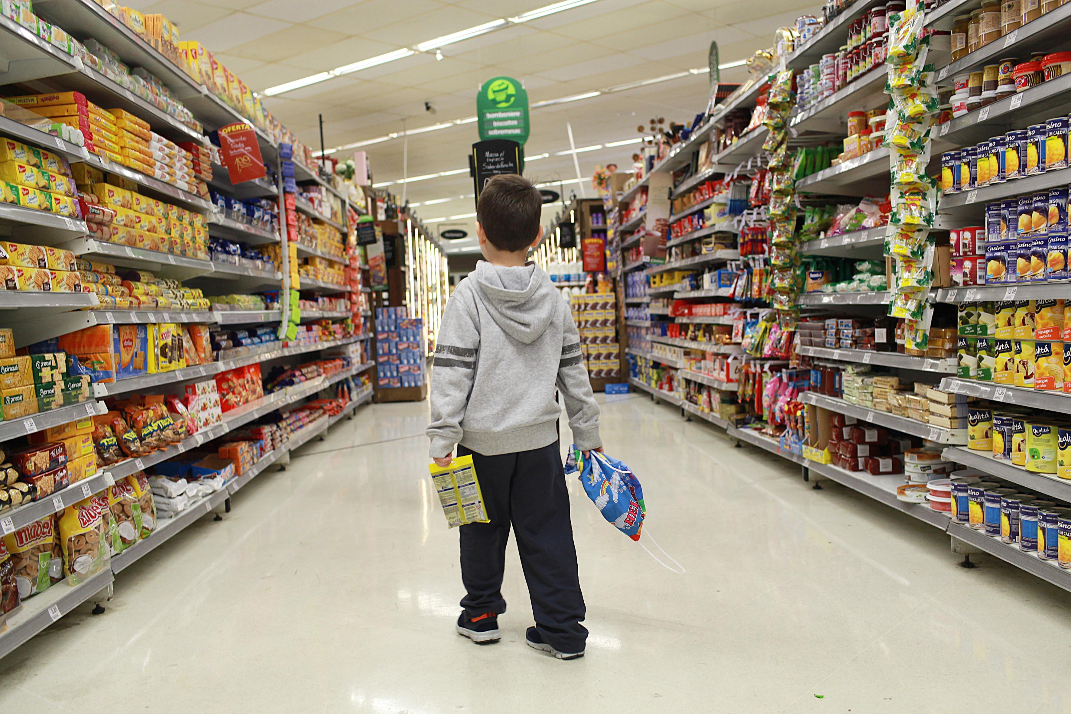Criança em corredor de mercado com várias propagandas (Foto: Mães de Peito)