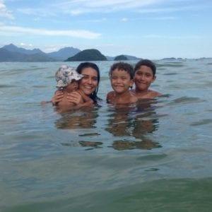 Marcela na praia com Gaia, 1, Damião, 6, e Samuel, 10