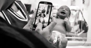 Recém-nascido é fotografado por familiar através de vidro (Foto: Bia Fotografia)